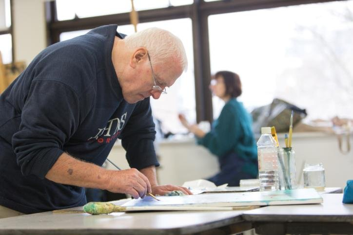 A learner experiments with watercolour at a workshop table in the WAES art studio