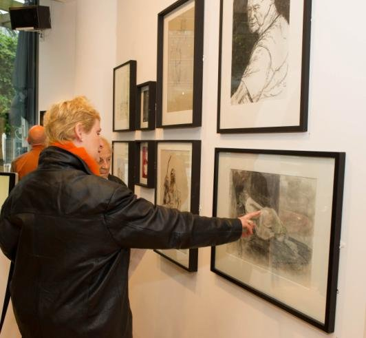 Visitors to the summer arts exhibition admire student drawings