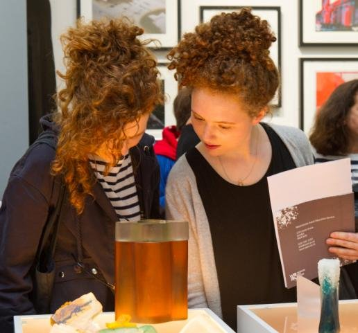 Exhibition visitors admire WAES glass students' work