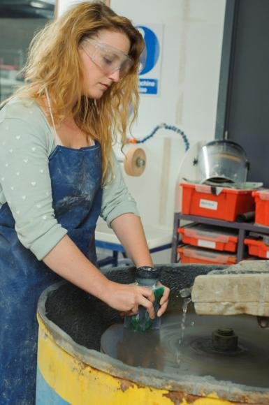 WAES glass student Jessie uses the large flatbed grinder in her work