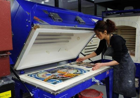 Lining up a design on the large flatbed fusing kiln
